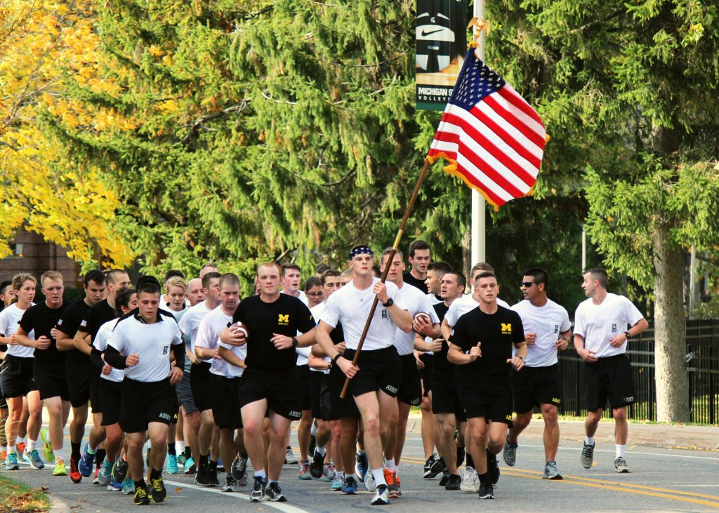 Several dozen U-M and MSU ROTC cadets running down the street carrying the game footballs and the US Flag
