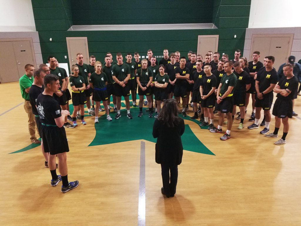 Juliana Powell stands in front of a group of dozens of MSU and U-M ROTC cadets on an indoor basketball court