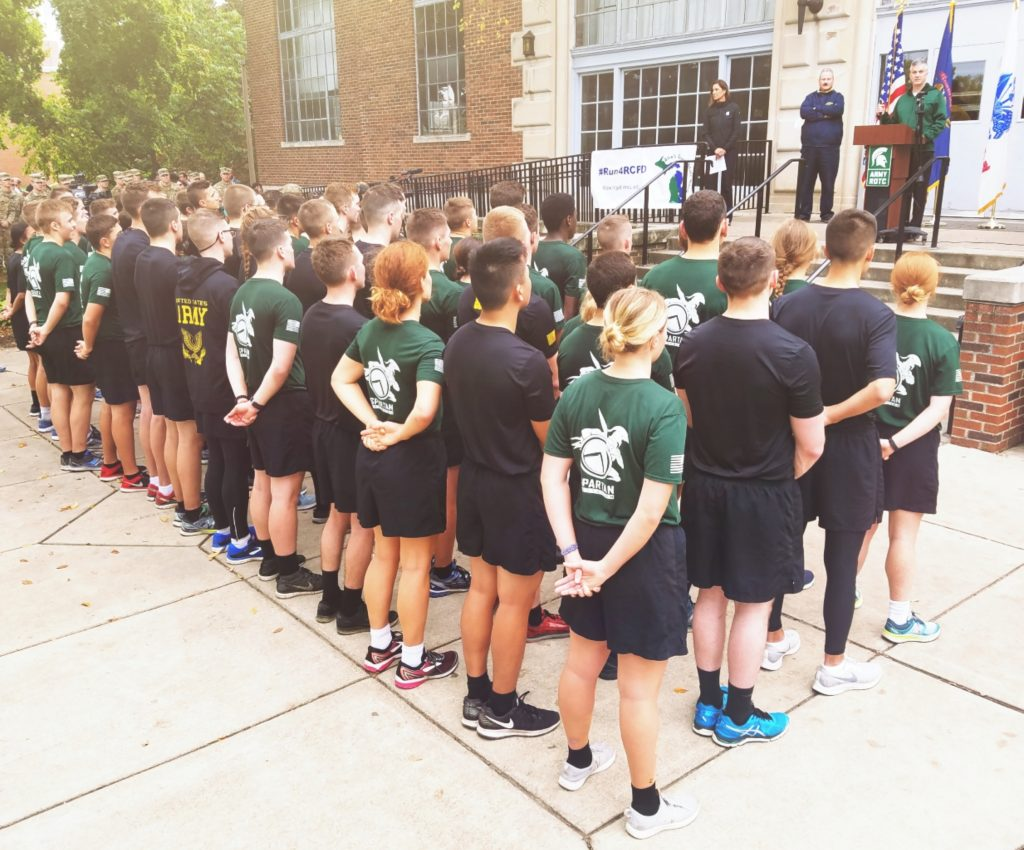 After the fifth annual Alex's Great State Race in the Fall of 2018, the combined MSU/U-M Army ROTC cadet corps stands in formation. They listen to speeches offered by disability service office directors from both schools during the Landing Ceremony on the steps of MSU's Demonstration Hall.