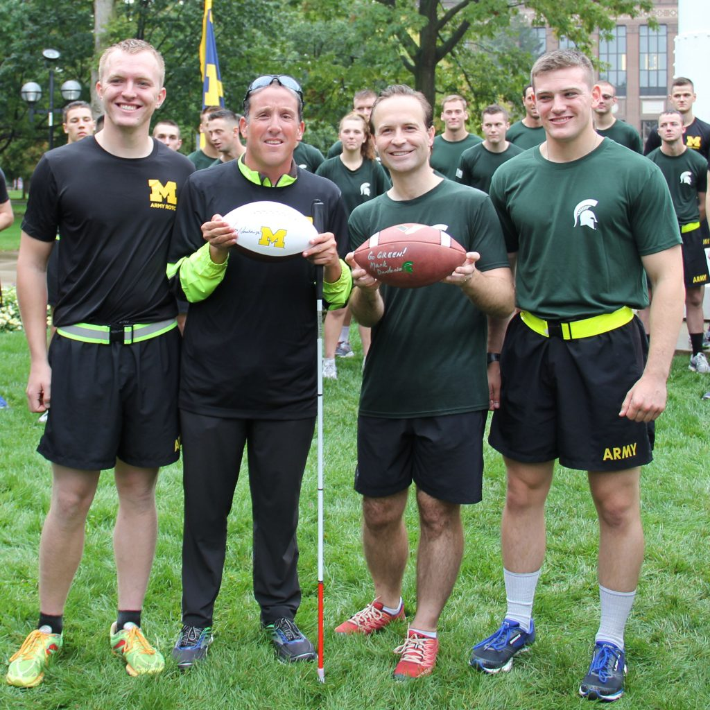 After the 4th Alex's Great State Race in 2017, participants Justice  Richard Bernstein and former Lt. Gov. Brian Calley present the official  rivalry game balls, joined by Army ROTC cadet runners.